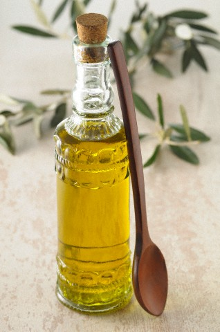Bottle of Olive Oil with Wooden Spoon --- Image by © Radius Images/Corbis